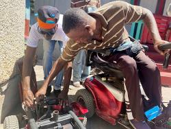 Lennox Edwards (right) fixing a motorised wheelchair at his home in Dunkirk, Kingston.