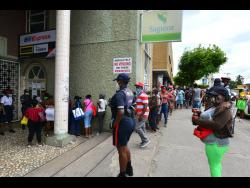 Persons waiting to get inside a Western Union outlet in Spanish Town in April.