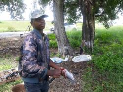 Jerome Dajue says he is not bothered by the minor cuts he gets when preparing fish for sale.