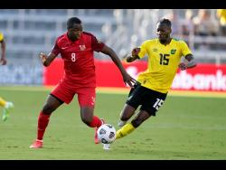 Jamaica's Blair Turgott (right) in action against Guadeloupe's Edwing Malpon during a Concacaf Gold Cup  match in Orlando, Florida on July 12, 2021.