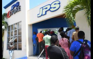 People gather outside JPS' Ruthven Road offices in Kingston on March 23.