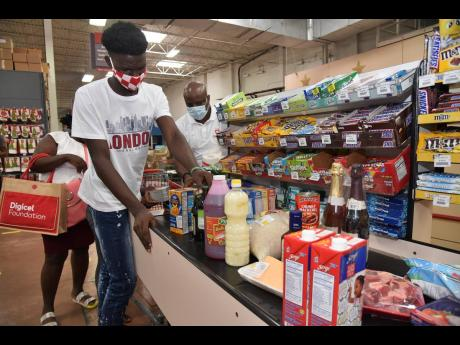 Tussan Smart (left) loads some of the groceries for the cashier with assistance from Digicel's Elon Parkinson (background).
