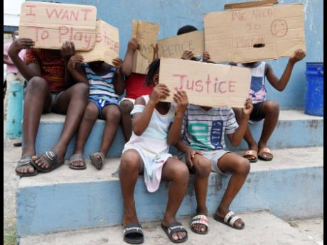 These children join the protest for peace in Wilton Gardens, Kingston, yesterday.