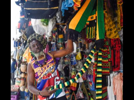 Jah Dale, a vendor in Half-Way Tree, St Andrew, shows off a few of his Jam wear.
