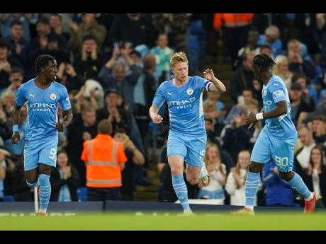 Manchester City's Kevin De Bruyne (centre) celebrates with teammates Romeo Lavia (right) and Joshua Wilson-Esbrand after scoring his team's first goal during the English League Cup third round match against Wycombe Wanderers yesterday. Manchester City won 6-1.